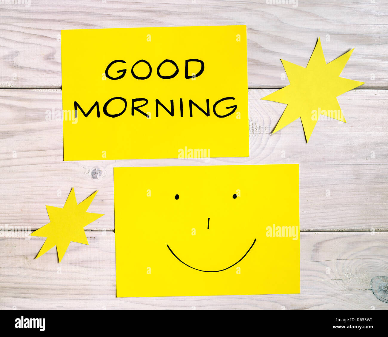 Text Good Morning And Smiley Face With Sun Shapes On Wooden Table