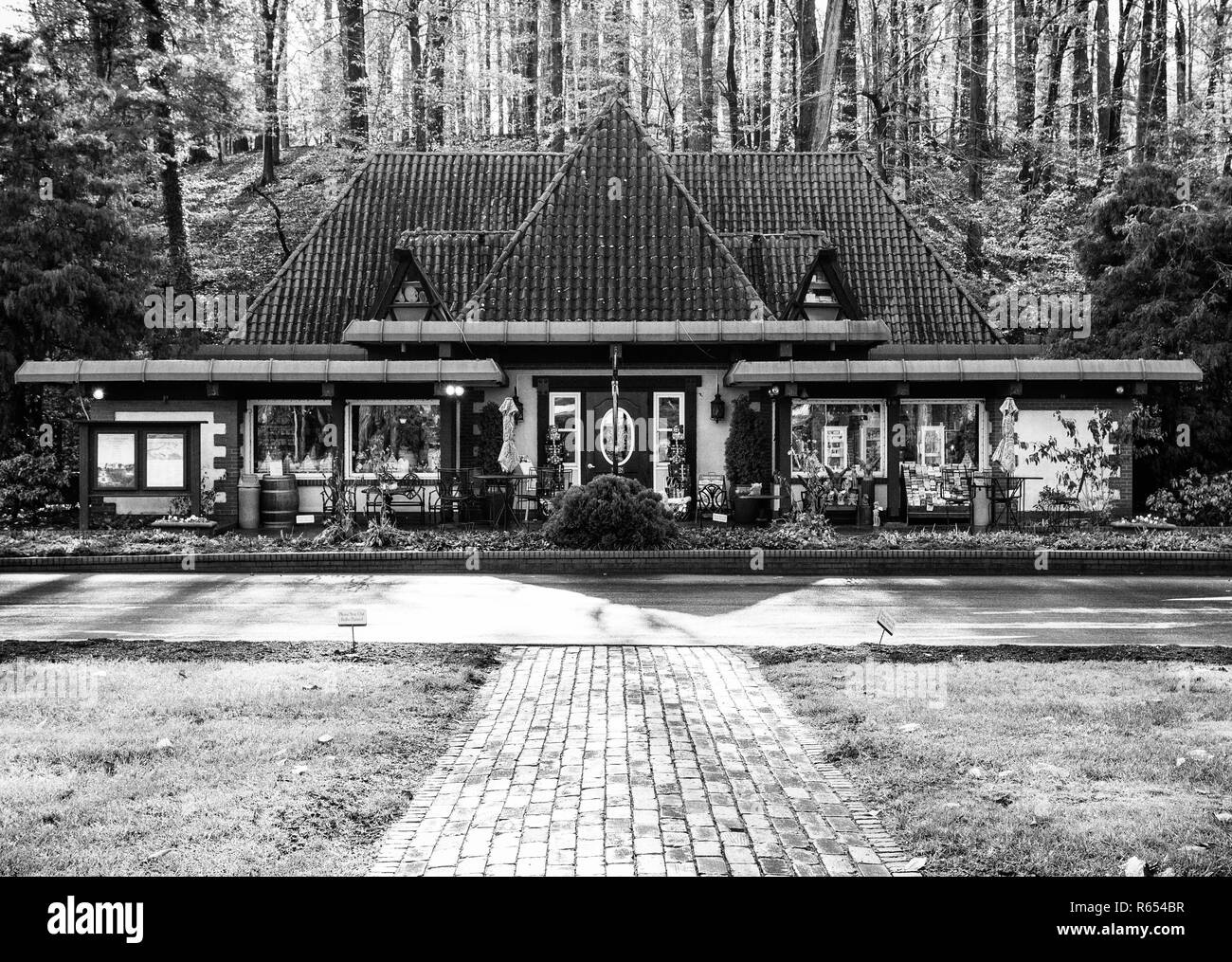 The Gate House Gift Shop is backlit in early morning against a backdrop of trees, at the Biltmore Estate in Asheville, NC, USA - Stock Image