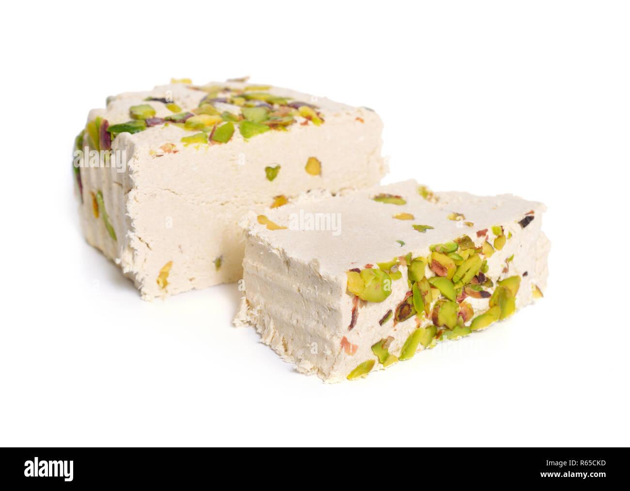 Tahini-based halva with pistachios. Isolated on white background. - Stock Image