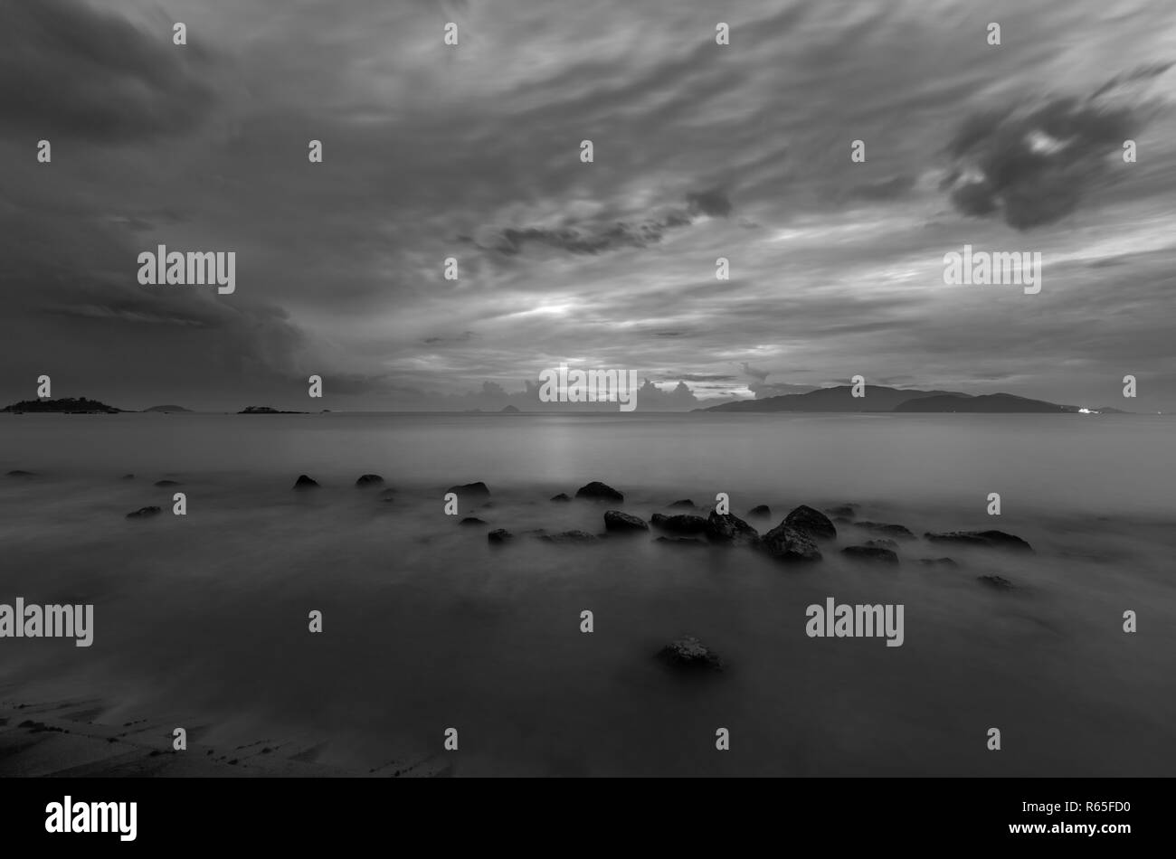 A moody black and white morning sky over Nha Trang bay Vietnam just before sunrise. - Stock Image