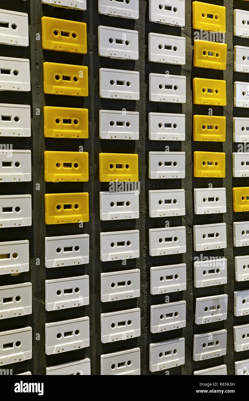 Wall decorated with white several music tapes - Stock Image