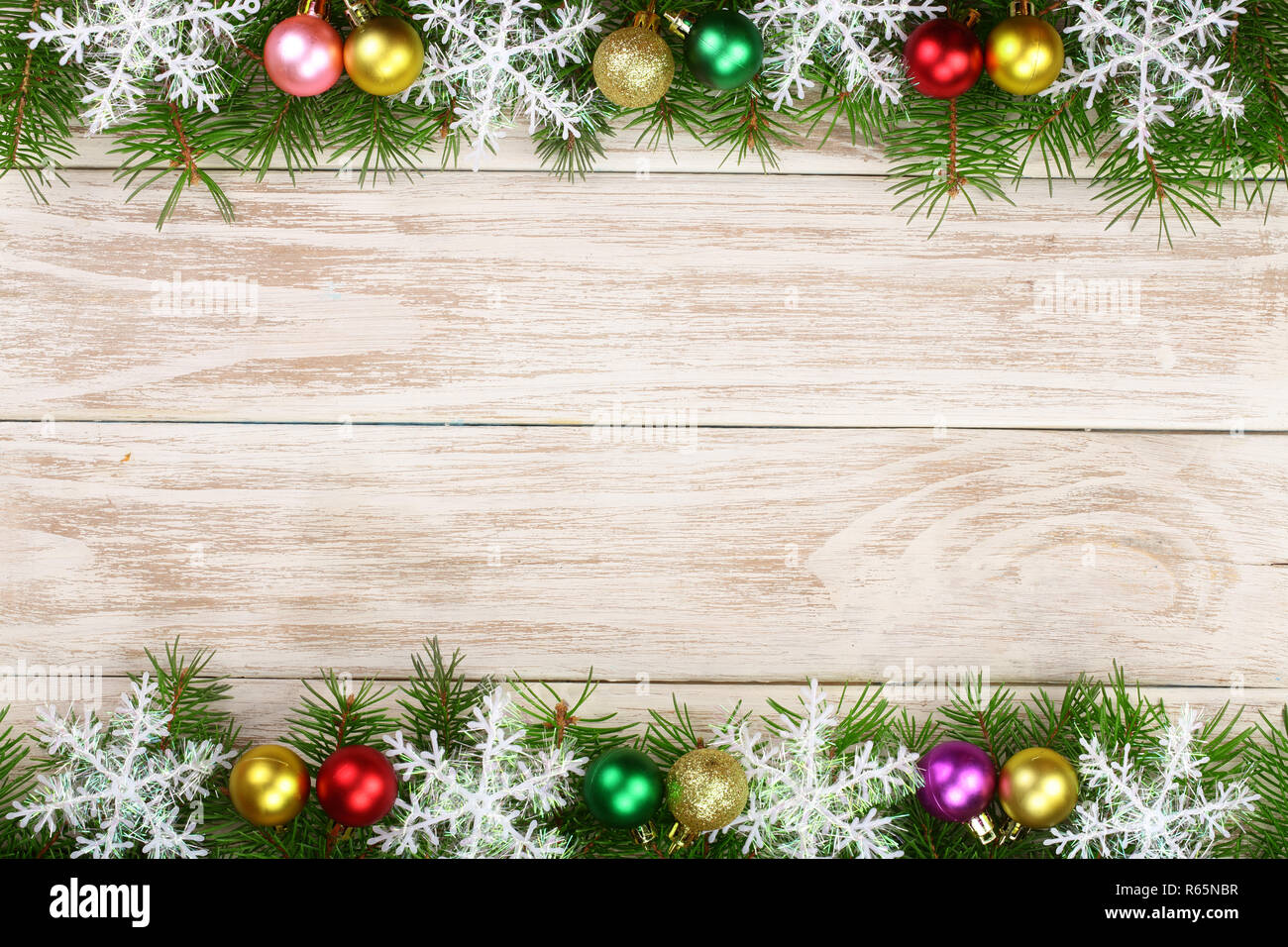 Christmas frame made of fir branches decorated with snowflakes and balls on a light wooden background - Stock Image