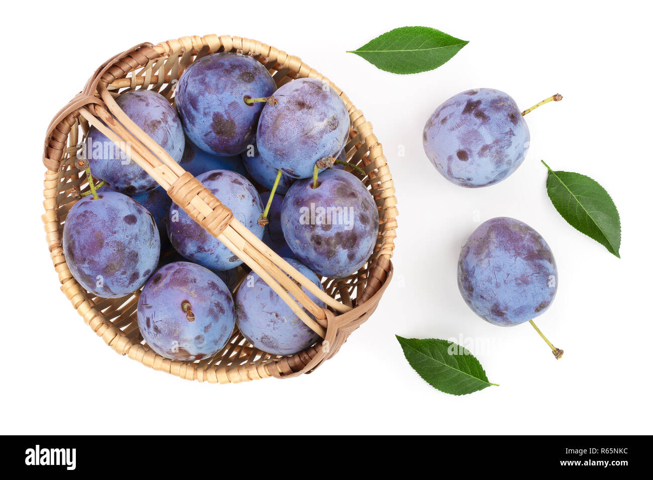 plums in wicker basket isolated on a white background. Top view. Flat lay pattern Stock Photo