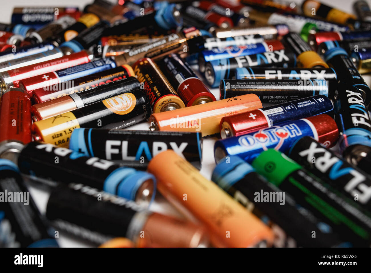 Arkhangelsk, Russia, December 3, 2018: A lot of alkaline batteries scattered on a white table. Concept of reuse, recycling, pollution of heavy metal salts, mercury, cadmium. - Stock Image
