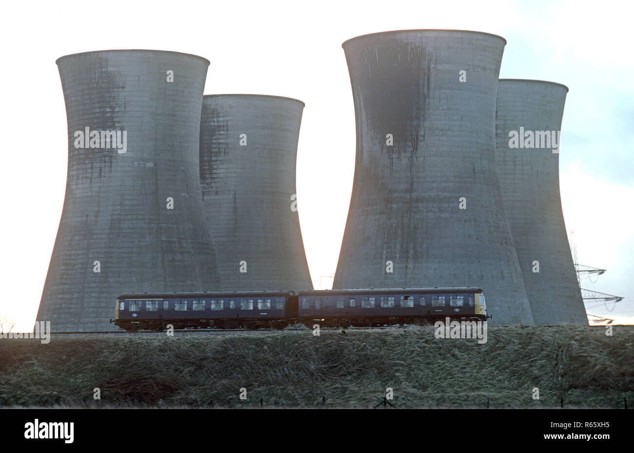 Diesel Multiple Unit passing in front of power station cooling towers on the British Rail Preston to Colne railway line, Lancashire, Great Britain - Stock Image