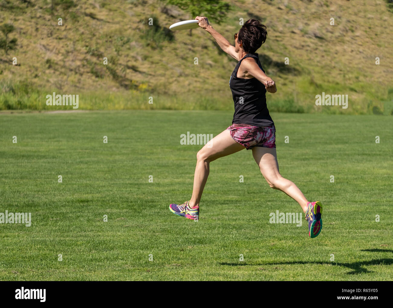 A very fit woman in her late 40's, running at full speed while playing sports, leaping into the air and catching a flying disc - Stock Image