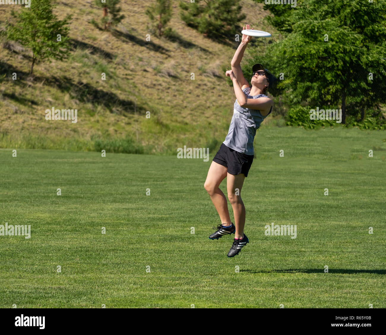 A young very fit woman leaps in the air, and concentrates as she catches a flying disc - Stock Image