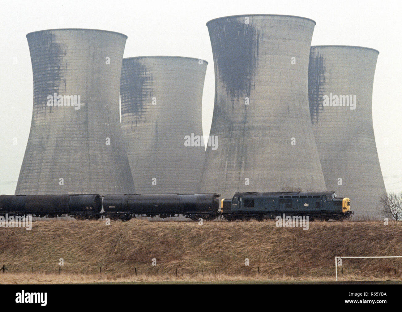 Diesel locomotive passing in front of power station cooling towers on the British Rail Preston to Colne railway line, Lancashire, Great Britain - Stock Image