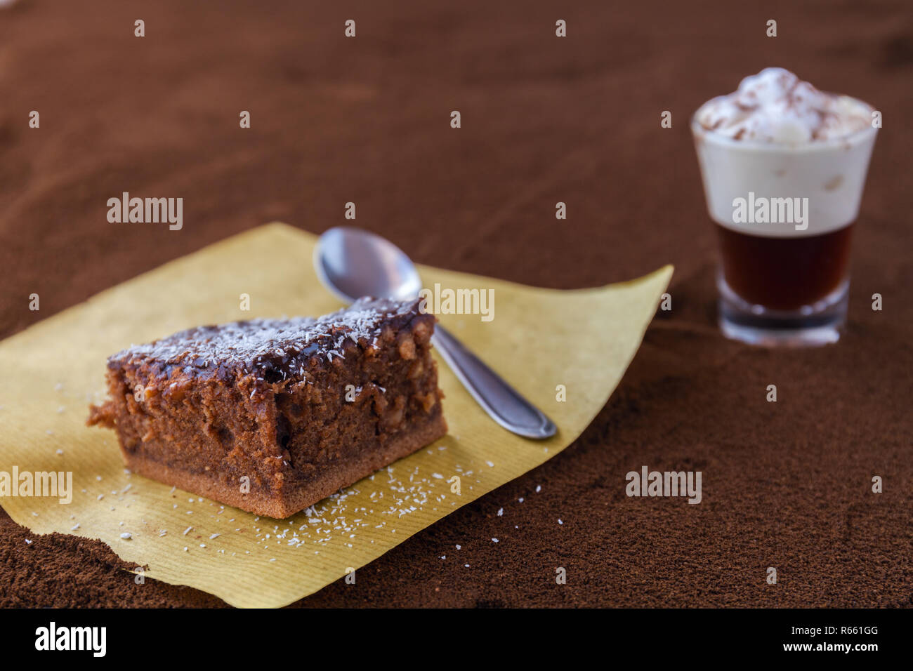 Little cup of piccolo latte macchiato on a table covered with ground coffee as a background and chocolate brownie with cocoa cream and coconut chips Stock Photo