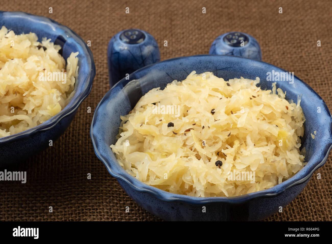 Sauerkraut in a blue bowl. Fresh healthy sauerkraut. - Stock Image