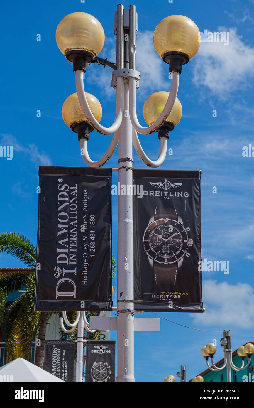Sign for Diamonds International and Breitling on street lamp in Antigua - Stock Image