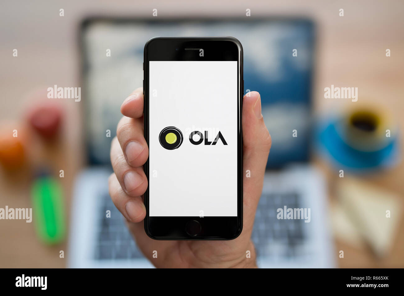 A man looks at his iPhone which displays the Ola Cabs logo, while sat at his computer desk (Editorial use only). - Stock Image