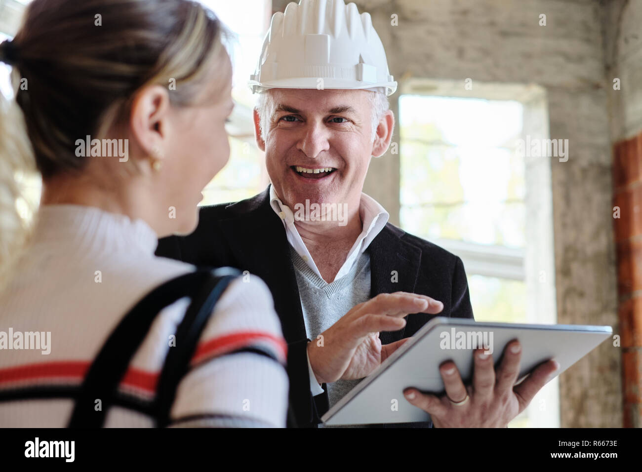 Woman Buying New Home And Talking To Broker Stock Photo
