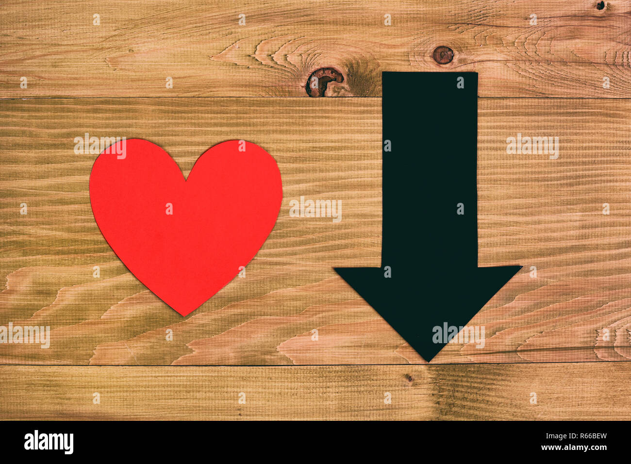 Red heart and arrow going down on wooden table,relationship breakup concept. - Stock Image
