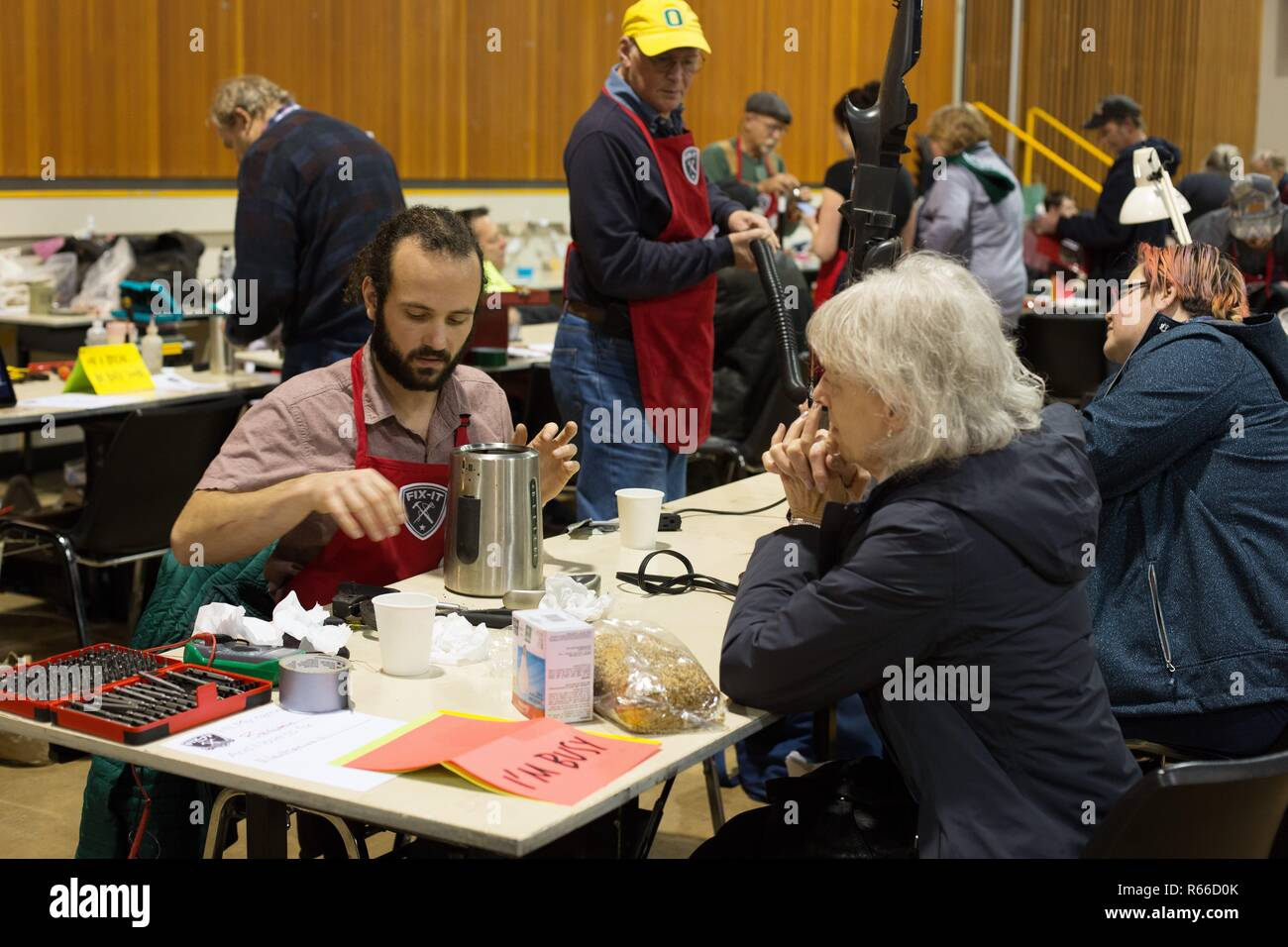 A volunteer fixer repairs a coffee maker at the Fix It Fair in Eugene, Oregon, USA. - Stock Image