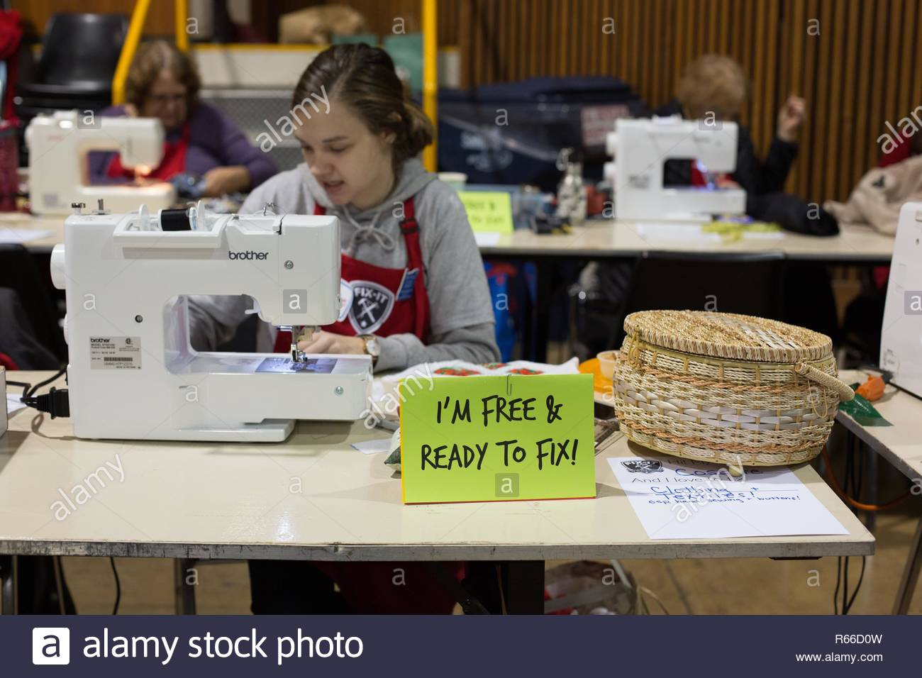 A volunteer works on an item at a sewing machine at the Fix It Fair in Eugene, Oregon, USA. - Stock Image