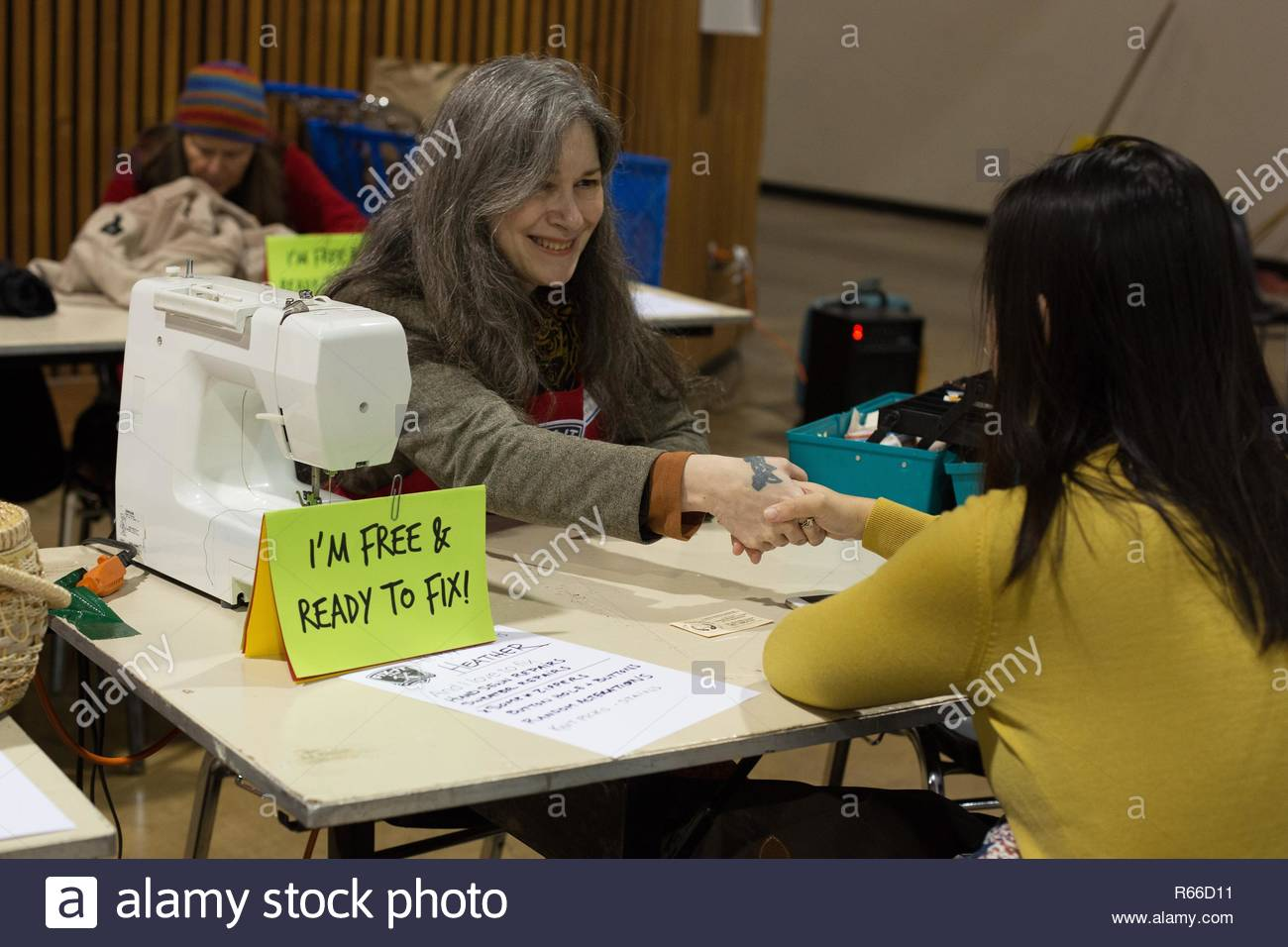 A volunteer 'fixer' greets a visitor to the Fix It Fair in Eugene, Oregon, USA. - Stock Image
