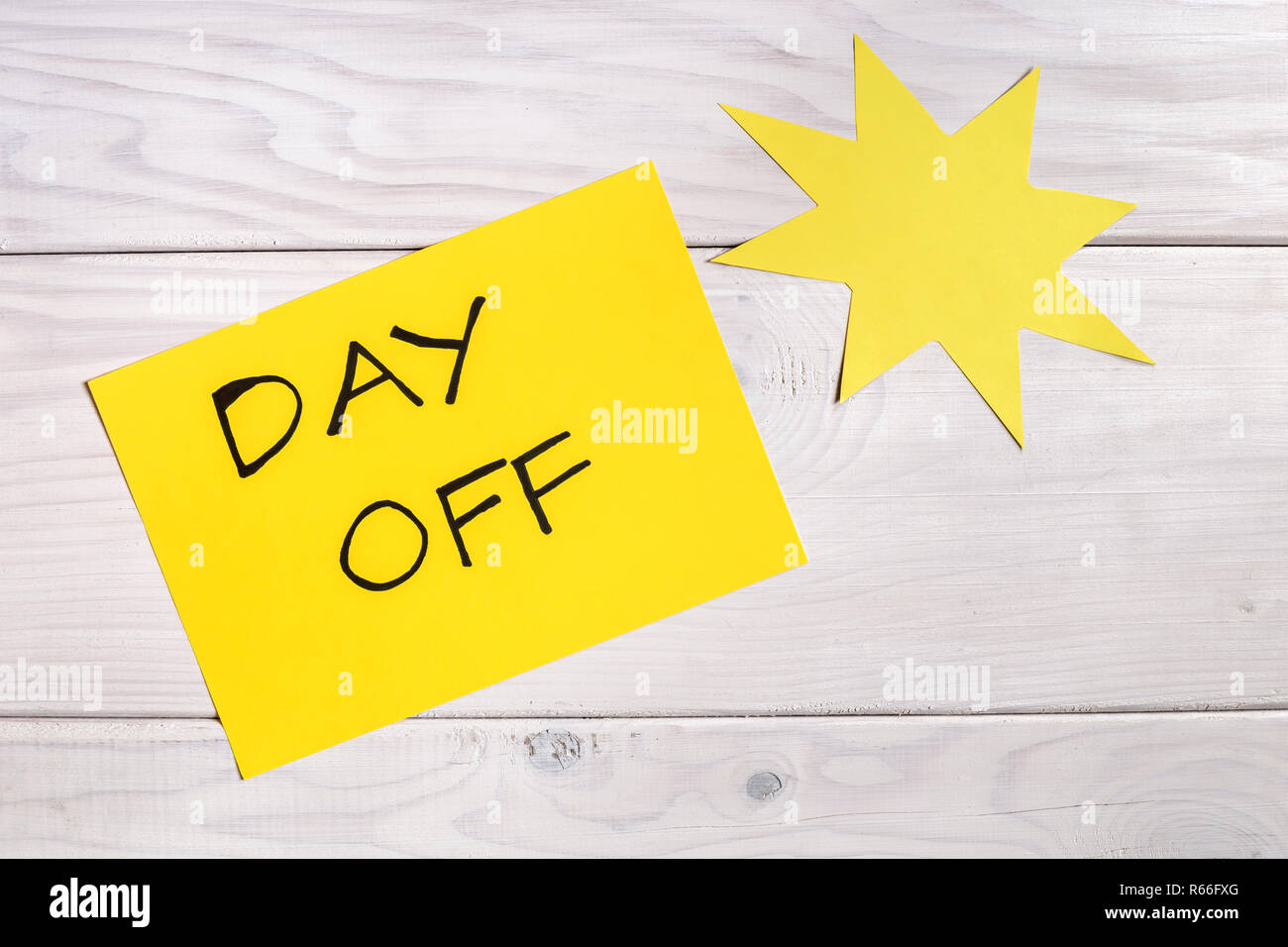 Text day off and sun shape on wooden table. - Stock Image