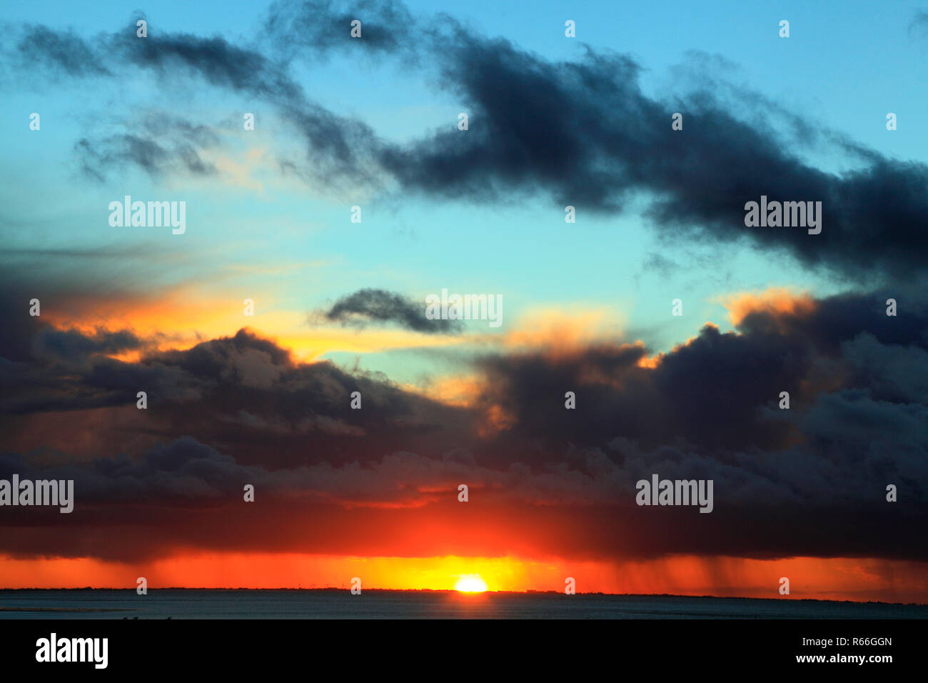 Sunset, red, blue, pink, sky, black clouds, gathering storm, weather, skies,  looking over The Wash, cloud formation, formations, Norfolk, UK - Stock Image