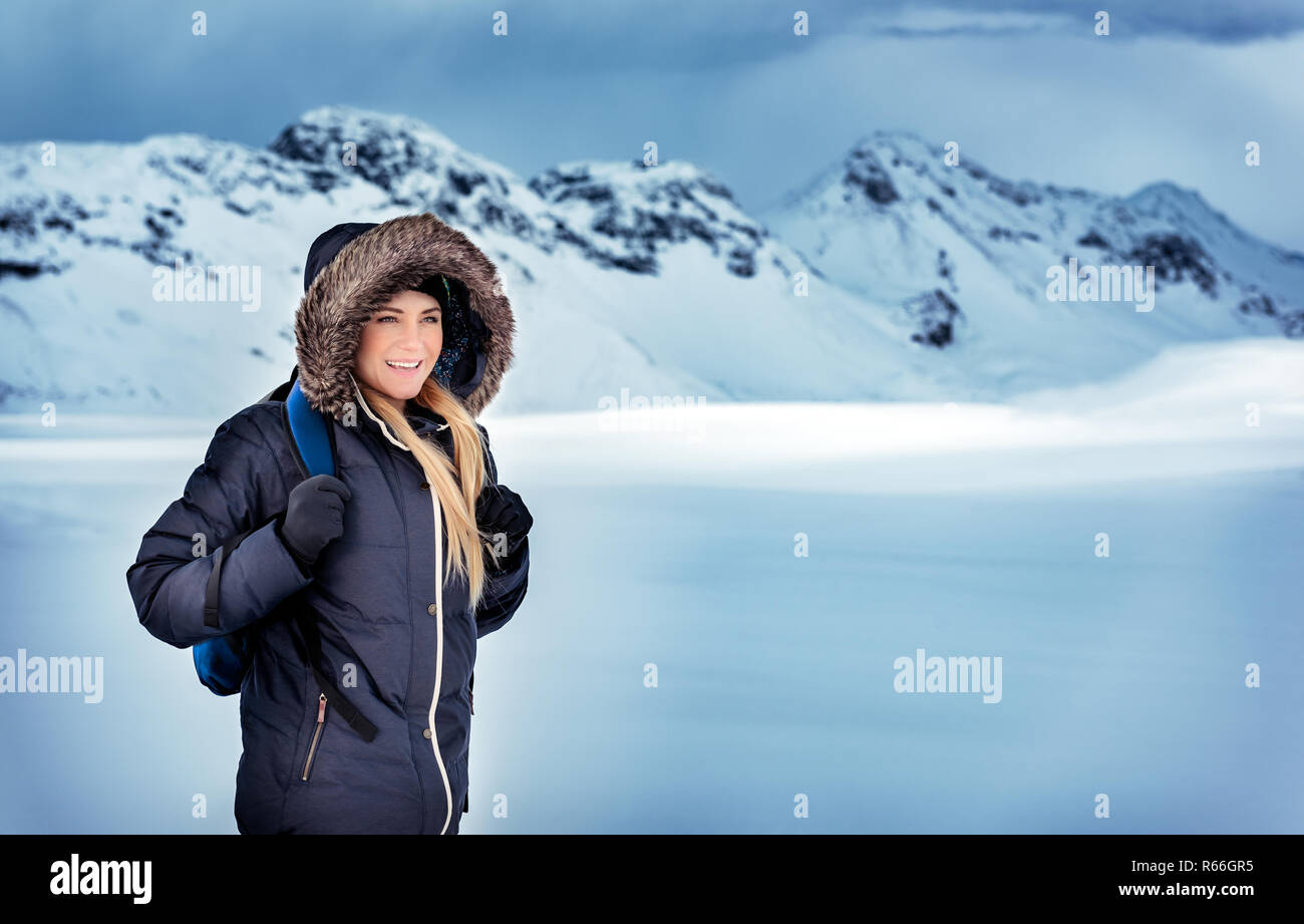 4208dc2b2d7 Happy beautiful woman with backpack traveling in the snowy mountains,  trekking in the North Pole, extreme winter holidays, Iceland