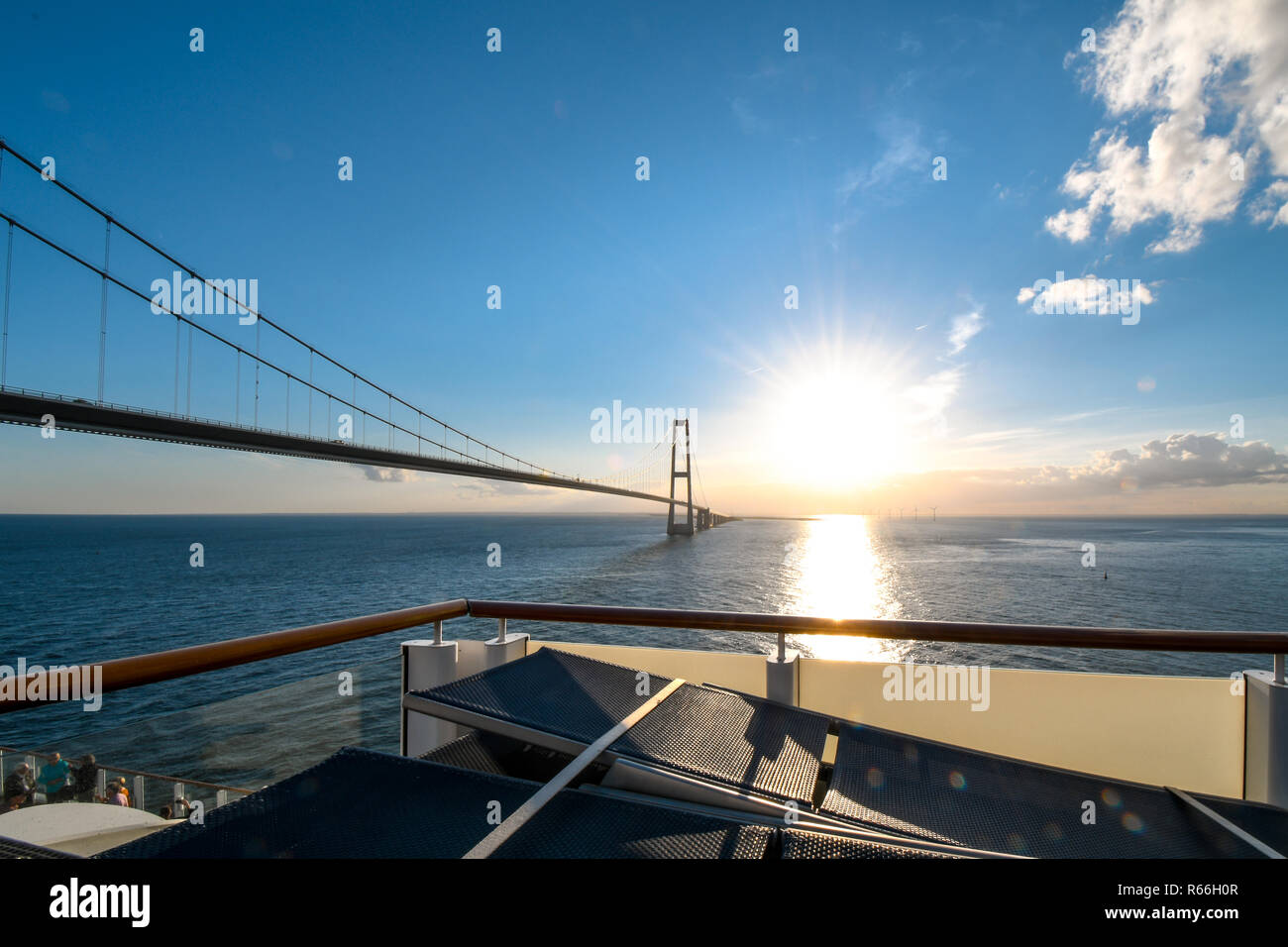 View of the setting sun over the Öresund Bridge which spans the strait between Sweden and Denmark from a boat on the Baltic Sea. Stock Photo