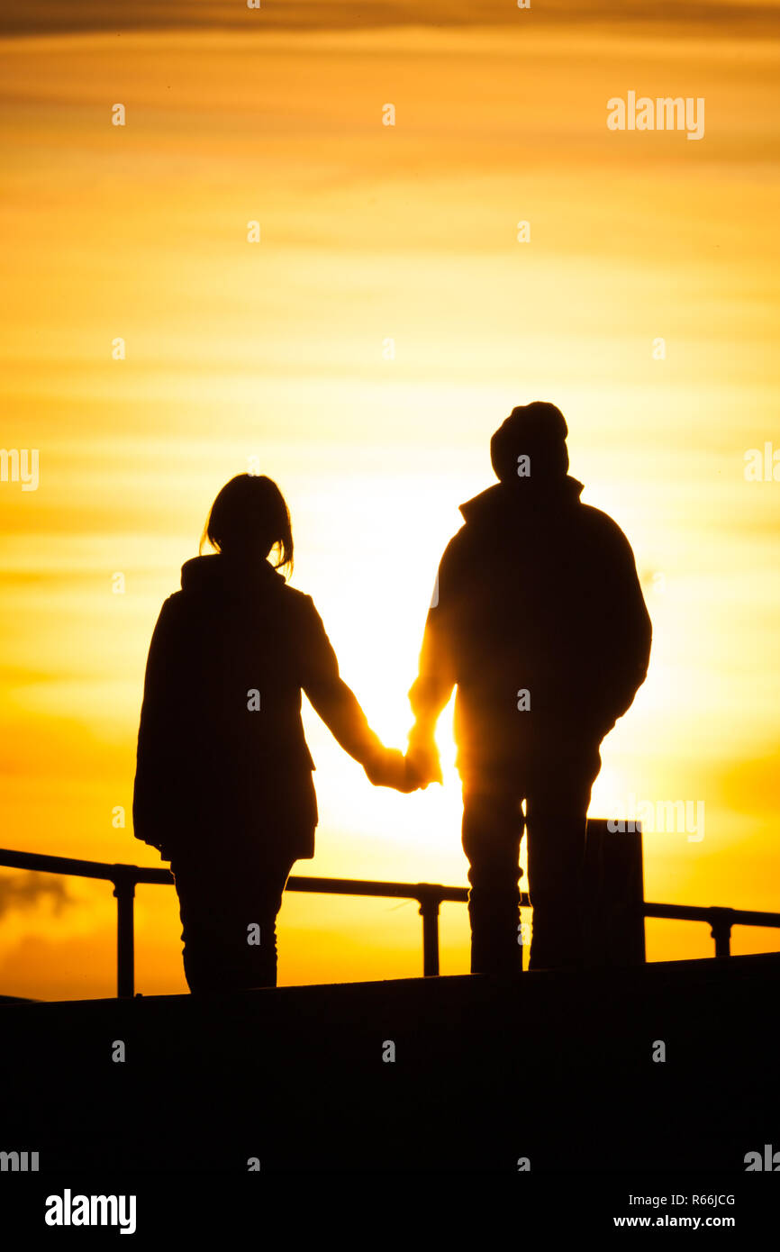 A couple (woman and man) in there late 20s, early 30s holding hands while they walk during sunset along the promenade in Southsea, UK - Stock Image