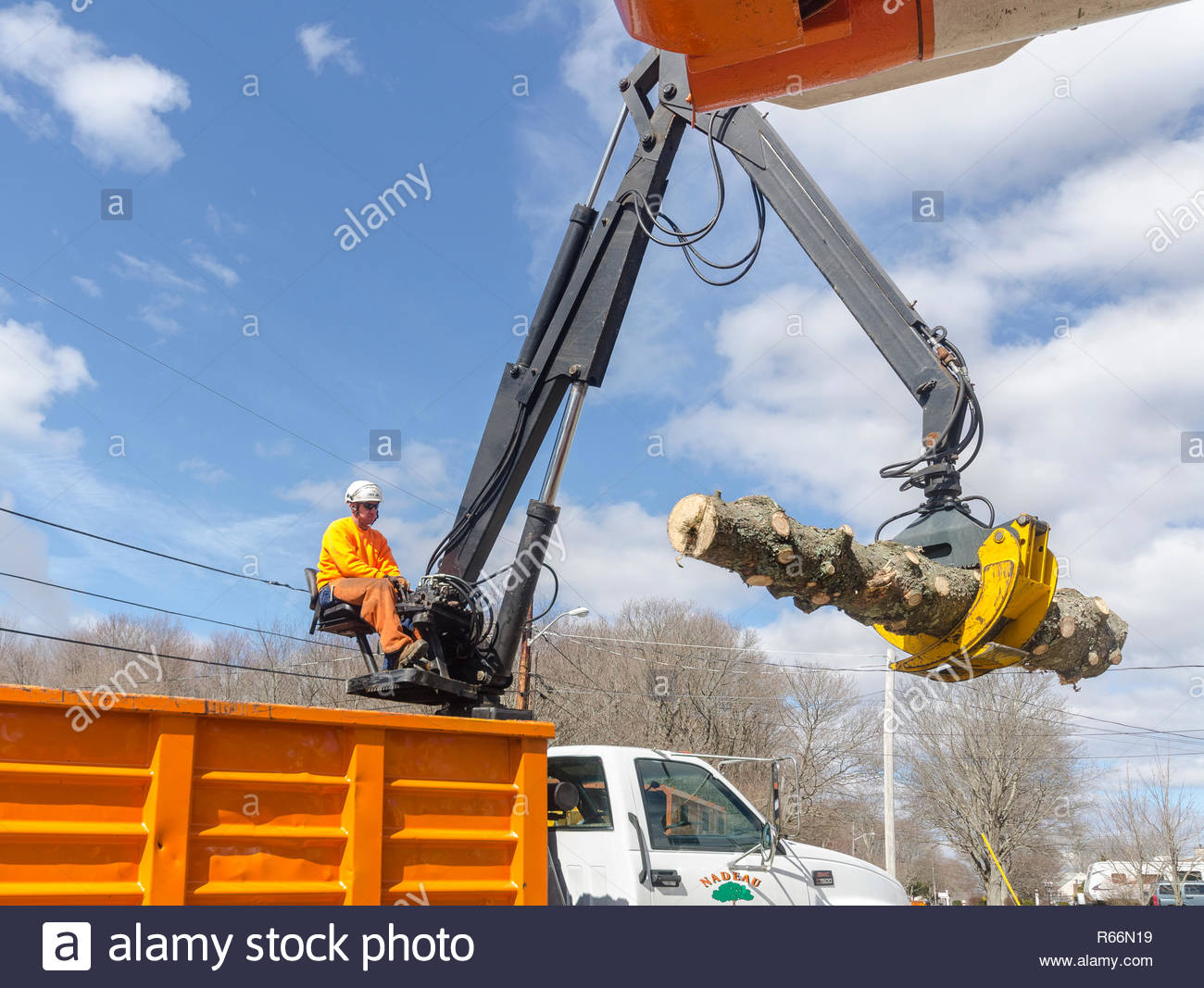 Somerset, Massachusetts, USA - March 31, 2015: Boom operator moving section of trunk of downed Norway Spruce tree to truck for removal - Stock Image