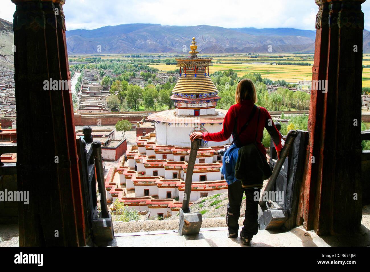 Female traveller looking at the Buddhist Kumbum chorten in Gyantse - Stock Image