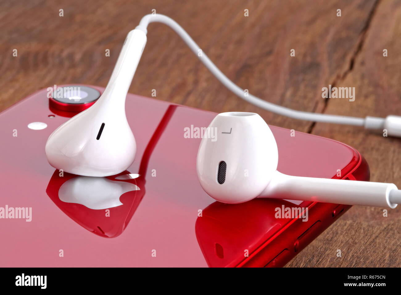 Koszalin, Poland – December 04, 2018: Red iPhone XR on a wooden table with white earphones. The iPhone XR is smart phone with multi touch screen produ Stock Photo