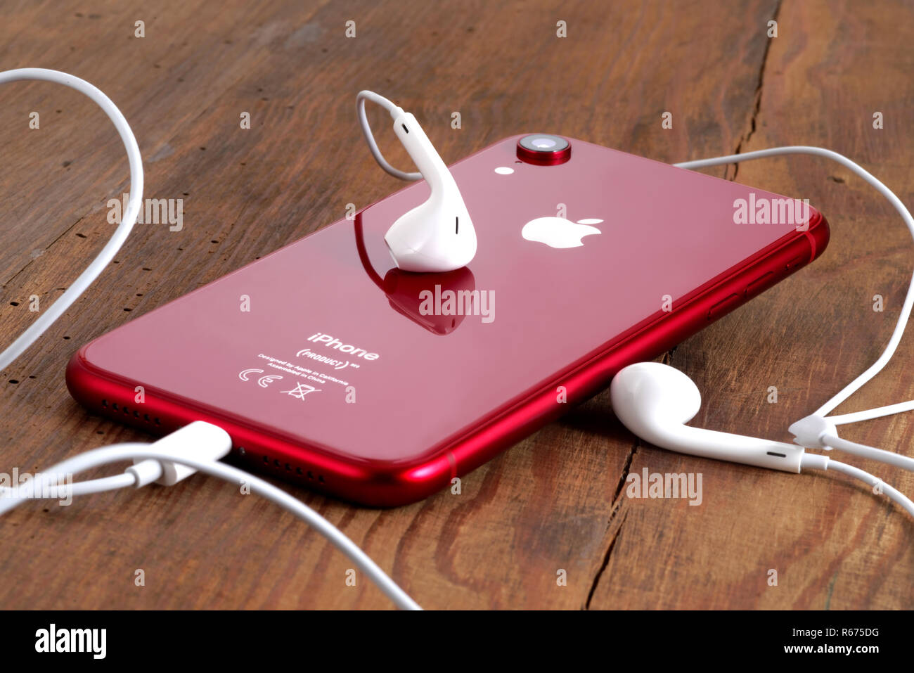 Koszalin, Poland – December 04, 2018: Red iPhone XR on a wooden table with white earphones. The iPhone XR is smart phone with multi touch screen produ - Stock Image