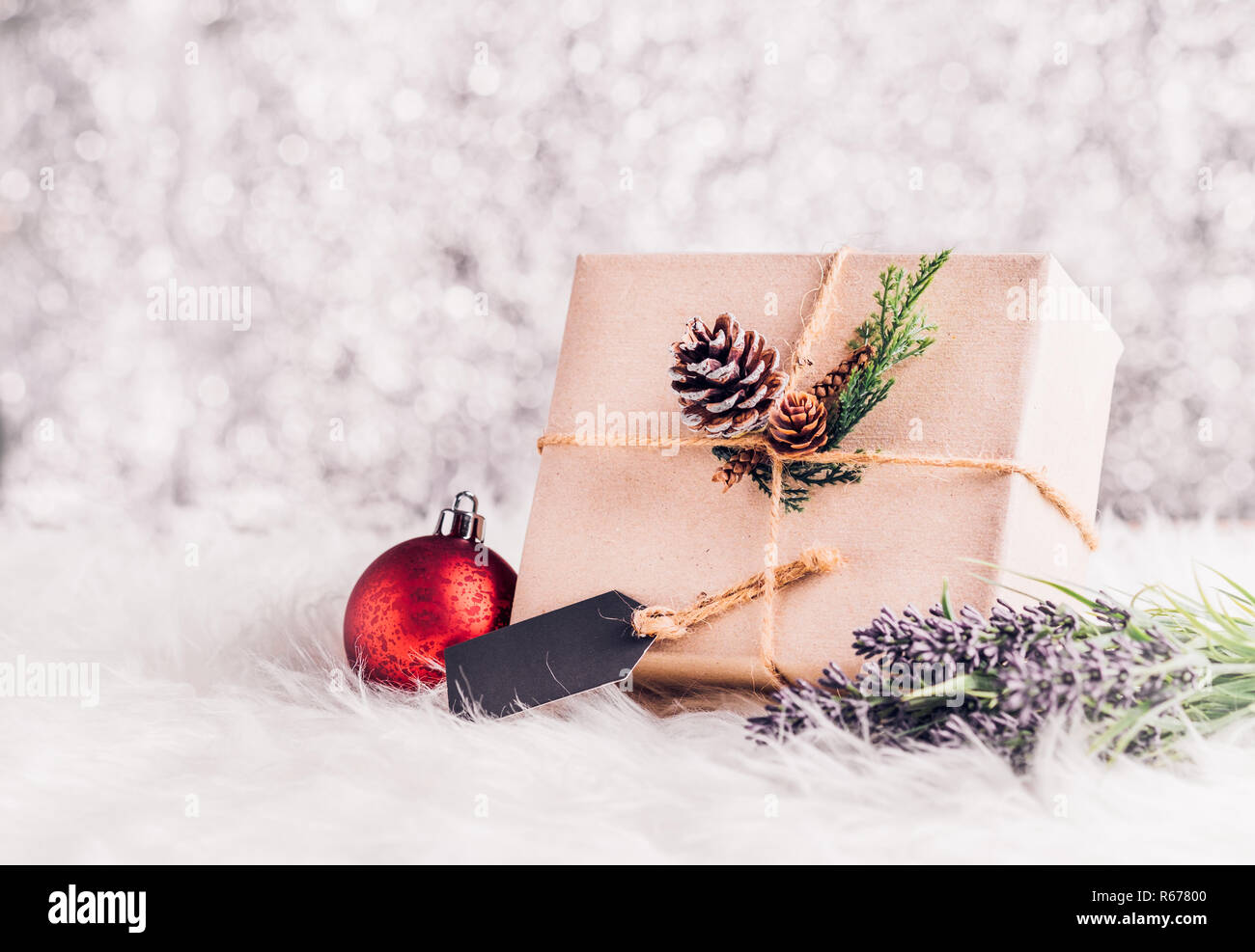 Brown paper craft warped on present box with label tag decorate with pine cone and christmas ball under xmas tree,Gift giving for holiday seasonal con - Stock Image