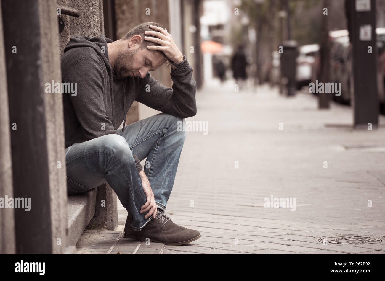 Young attractive man suffering from depression stress sitting alone and sad on the street feeling anxious and lonely in unemployment Mental health Dru - Stock Image