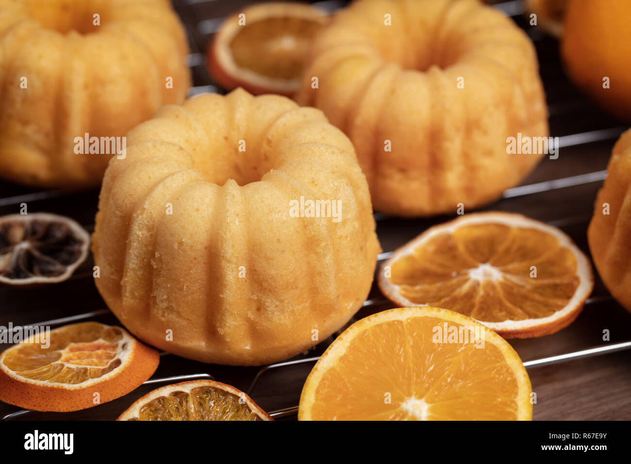 Small orange bundt cakes with fresh and dry oranges on cooling ruck, close up Stock Photo