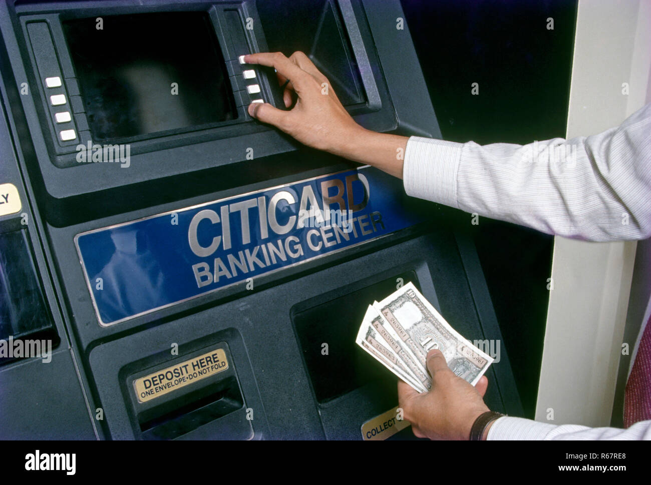 Close up of hand holding Ten Rupees Notes and push buttons of ATM machine, automated bank system - Stock Image