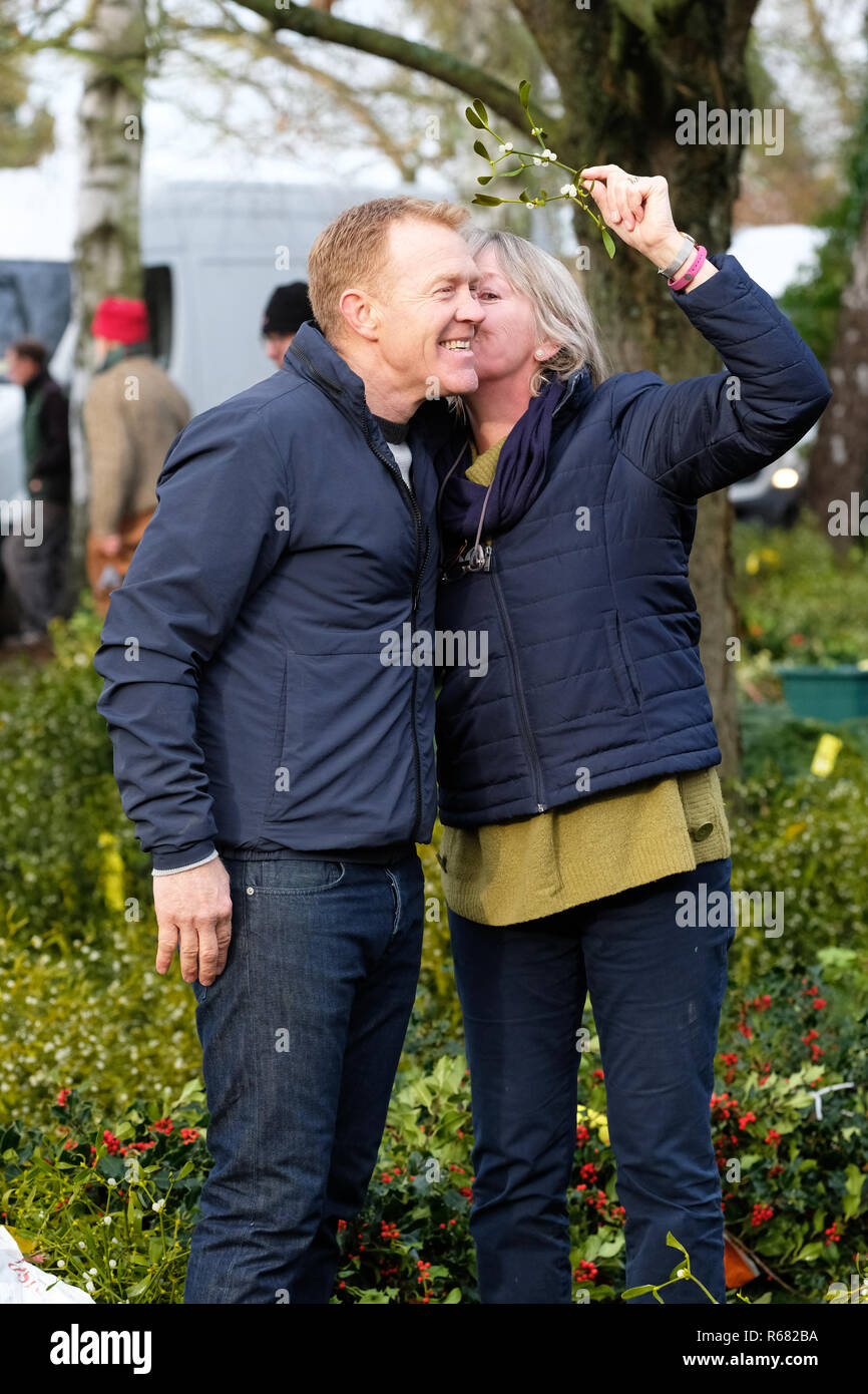 Burford House, Tenbury Wells, Worcestershire, UK - Tuesday 4th December 2018 - Christmas Holly and Mistletoe auction - Mistletoe auctions have been held in Tenbury Wells for over 160 years. TV celebrity Adam Henson receives a Xmas kiss under the mistletoe from a fan during a break in recording a feature for the Christmas edition of the BBC Countryfile program - Credit: Steven May/Alamy Live News - Stock Image