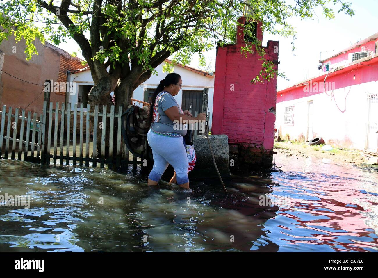 Asuncion, Paraguay. 04th Dec, 2018. A woman walks on a flooded street, in Asuncion, Paraguay, 04 December 2018. Numerous inhabitants of the neighborhood known as 'Banado Sur' are forced to live in unhygienic conditions due to the stagnant water of the floods caused by the rise of the Paraguay river, which have forced 7,500 families to evacuate their homes. Credit: Andres Cristaldo/EFE/Alamy Live News - Stock Image