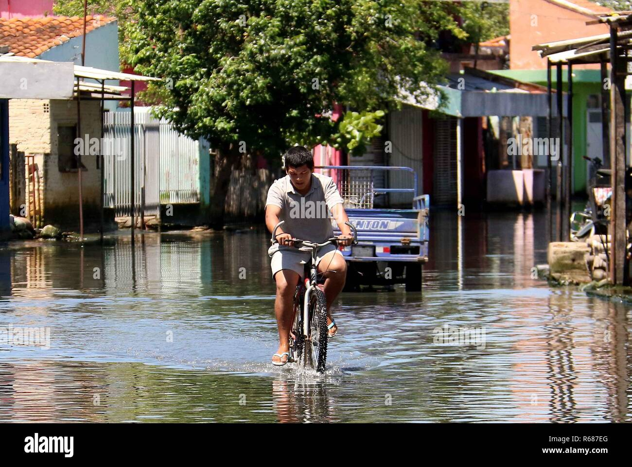 Asuncion, Paraguay. 04th Dec, 2018. A man rides a bike on a flooded street, in Asuncion, Paraguay, 04 December 2018. Numerous inhabitants of the neighborhood known as 'Banado Sur' are forced to live in unhygienic conditions due to the stagnant water of the floods caused by the rise of the Paraguay river, which have forced 7,500 families to evacuate their homes. Credit: Andres Cristaldo/EFE/Alamy Live News - Stock Image