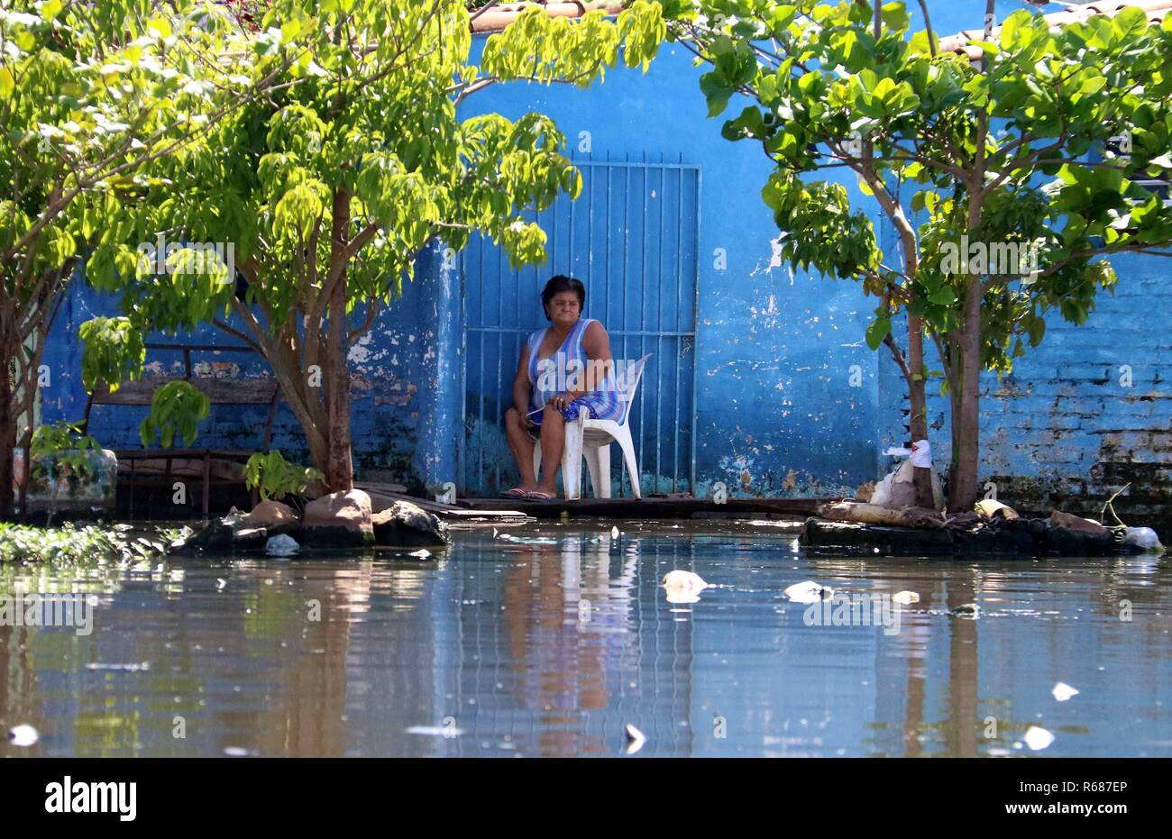 Asuncion, Paraguay. 04th Dec, 2018. A woman remains at her home on a flooded street, in Asuncion, Paraguay, 04 December 2018. Numerous inhabitants of the neighborhood known as 'Banado Sur' are forced to live in unhygienic conditions due to the stagnant water of the floods caused by the rise of the Paraguay river, which have forced 7,500 families to evacuate their homes. Credit: Andres Cristaldo/EFE/Alamy Live News - Stock Image