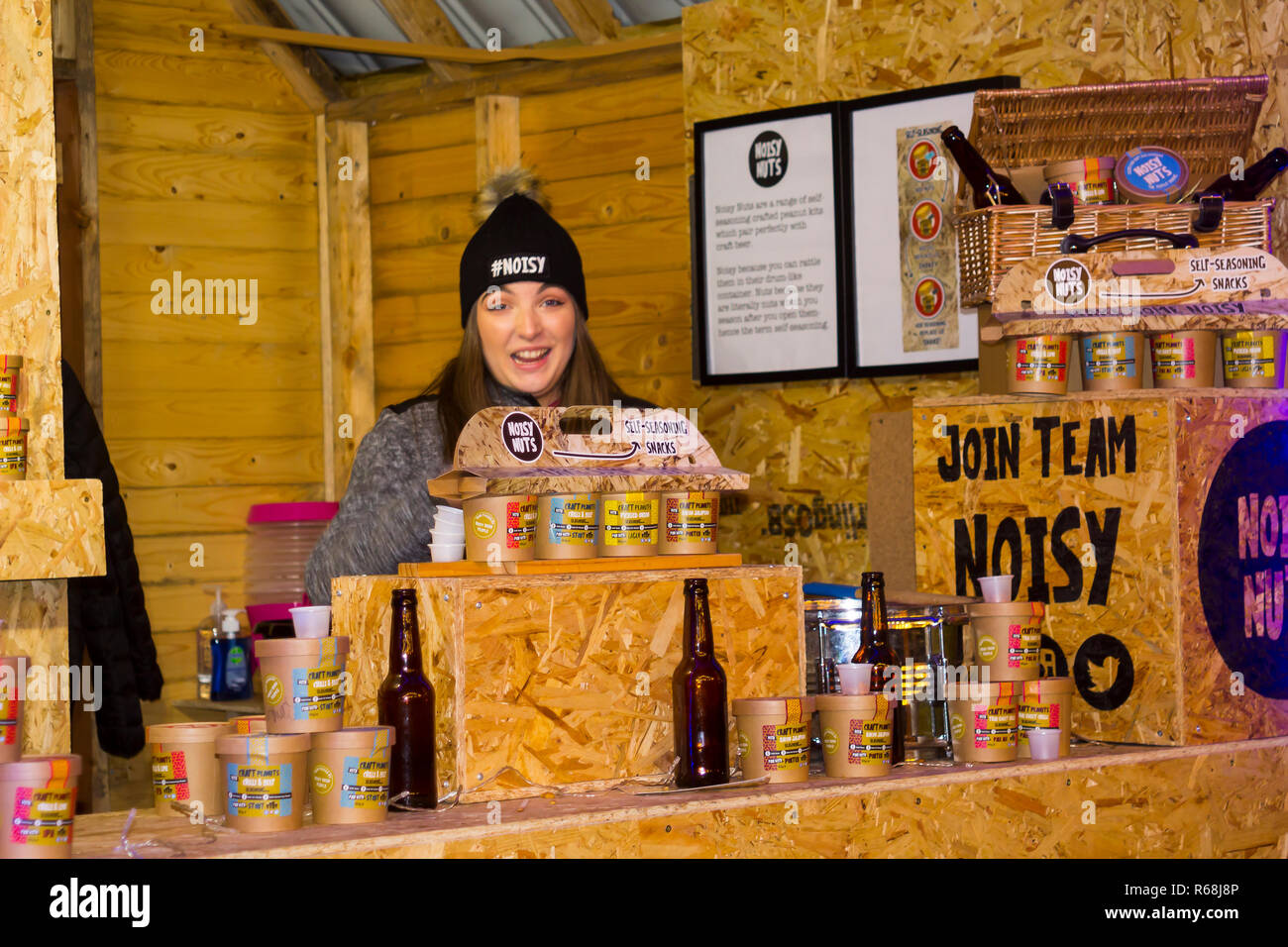 30 November 2018 A young women vendor selling nuts iat the Belfast Christmas Fair in Northern Ireland. The fair is now a popular annual event in the c - Stock Image