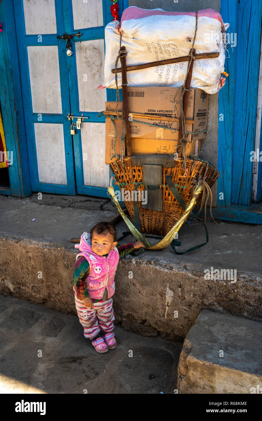 Nepal, Lukla, small child below large load to be carried by porter to Namche Bazaar - Stock Image