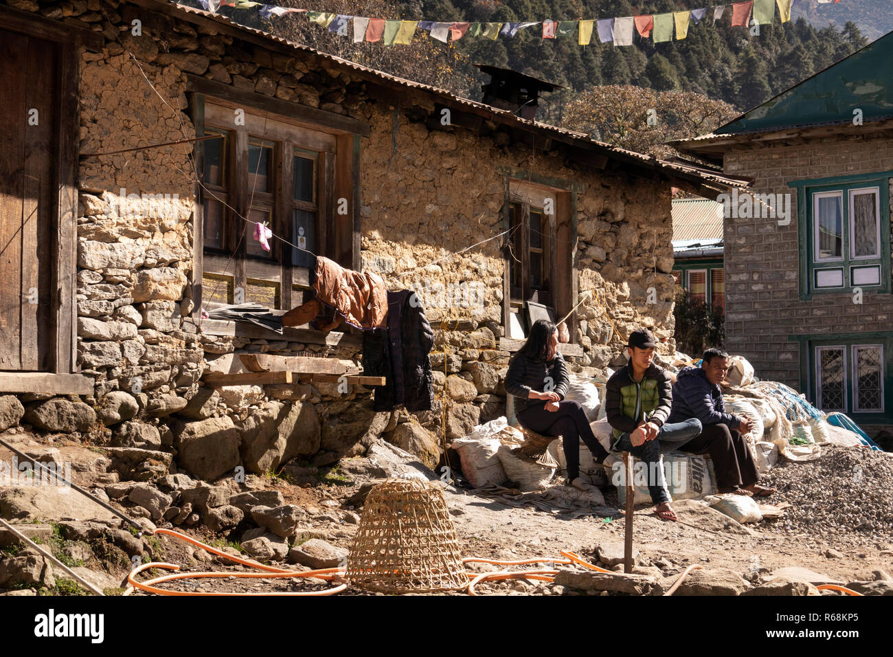 Nepal, Lukla, people sat outside traditional old, stone-built house in middle of village - Stock Image