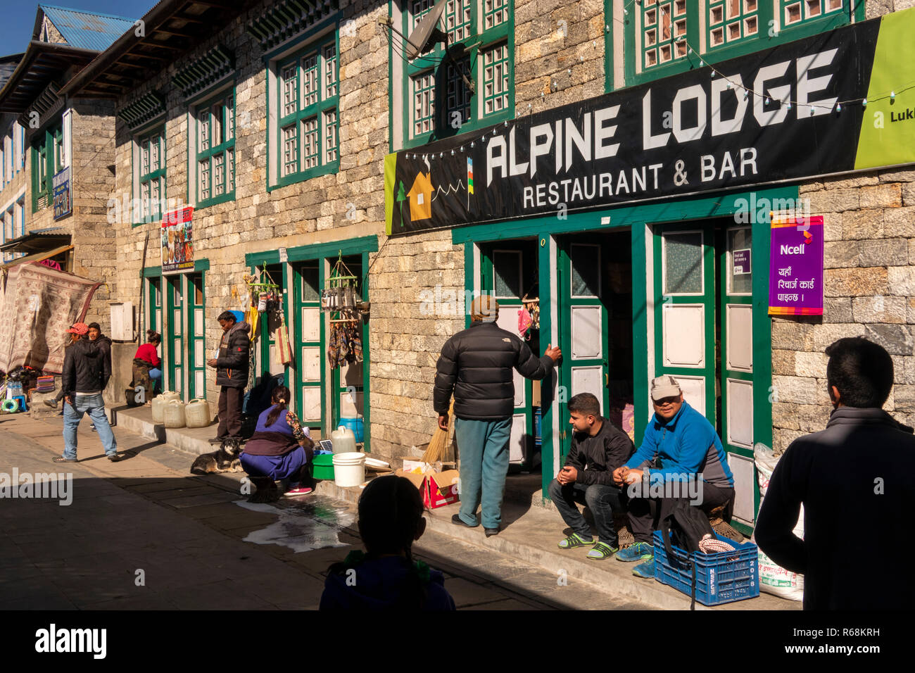 Nepal, Lukla, main street, people in sunshine outside Alpine Lodge restaurant and bar - Stock Image