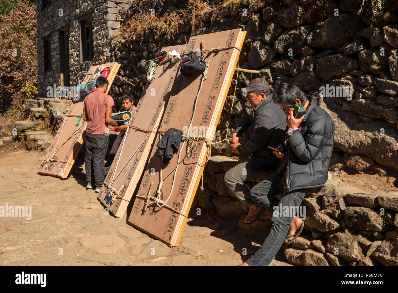 Nepal, Lukla, Lomdza, porters carrying loads of plywood resting beside path - Stock Image