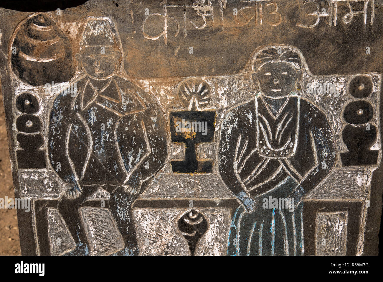 Nepal, Lukla, Lomdza, Buddhist folk art, figures of Nepali man and woman at temple altar carved in slate on Mani Wall - Stock Image