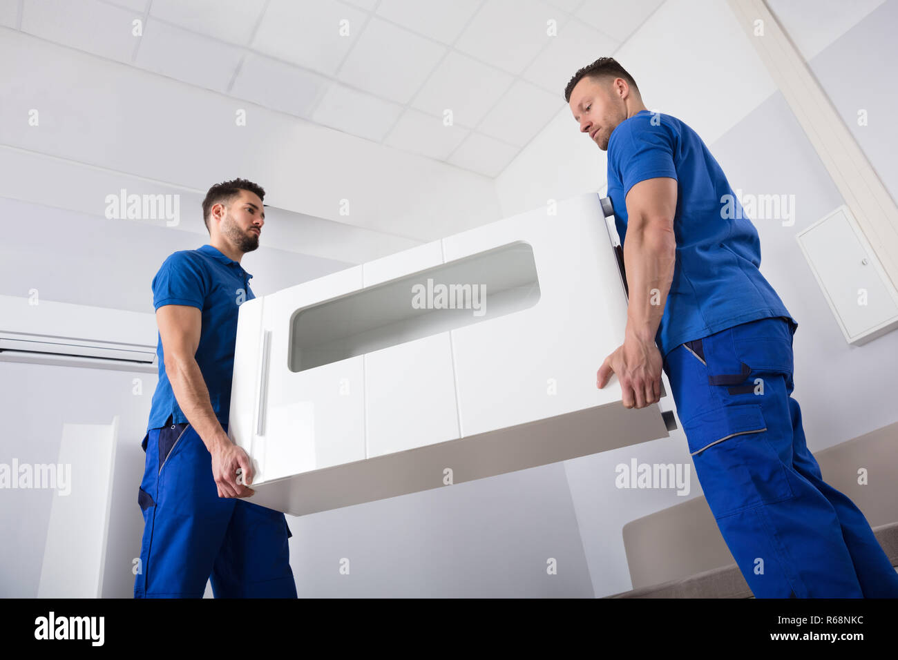 Two Movers Holding Furniture In Living Room Stock Photo