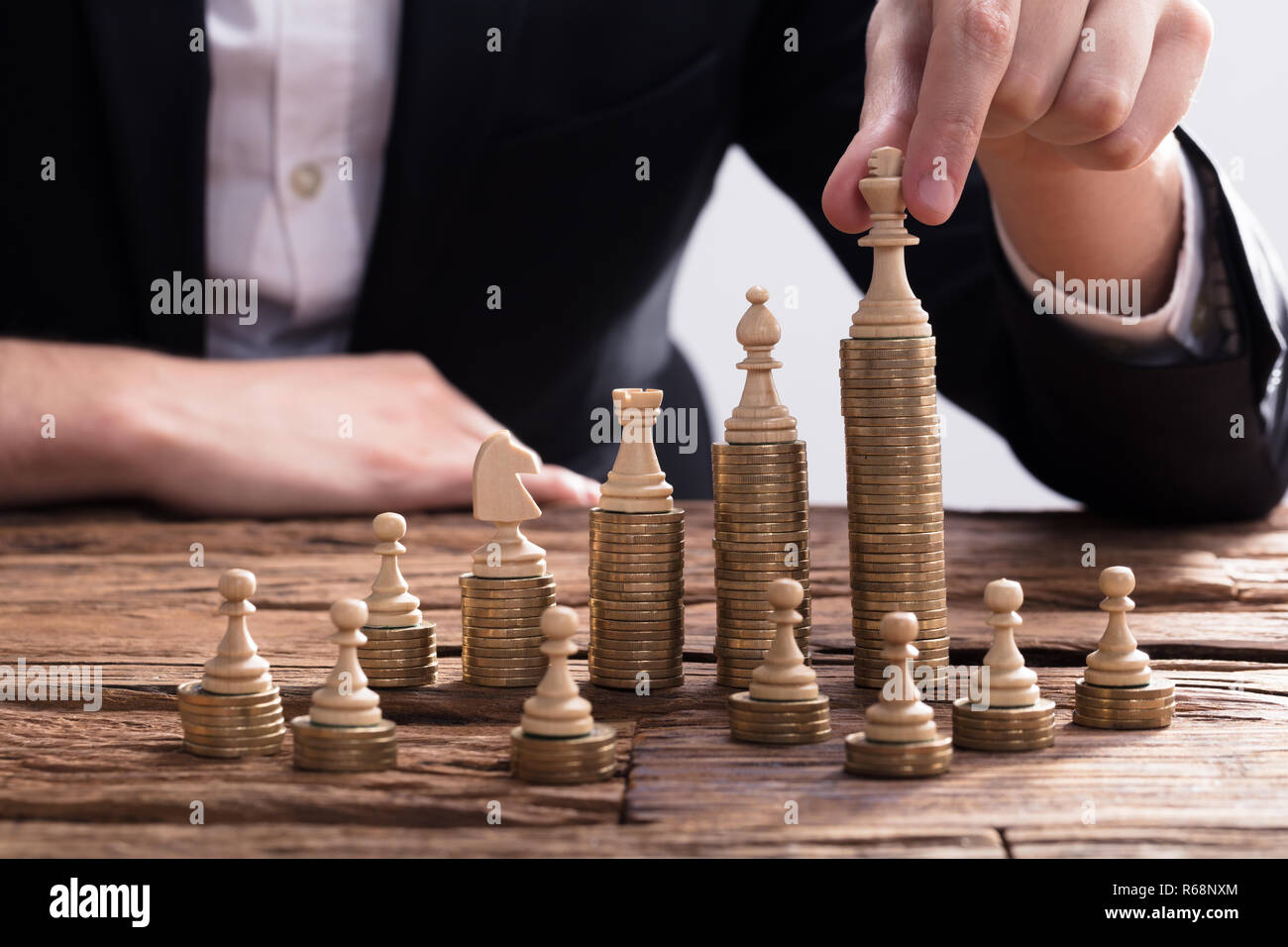 Businessperson Arranging Chess Piece On Stacked Coins - Stock Image