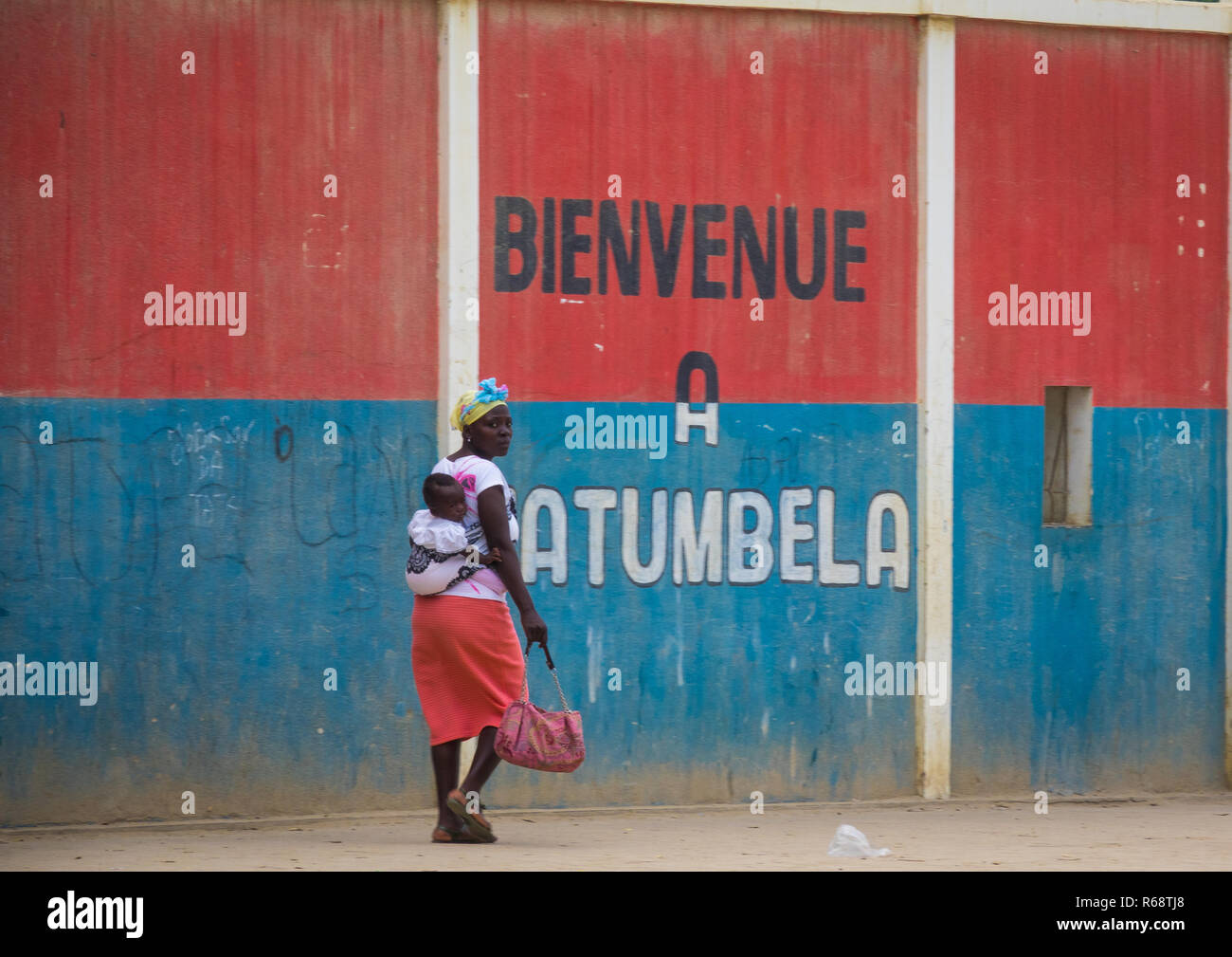 Woman walking in front of a wall with a welcome slogan, Benguela Province, Catumbela, Angola - Stock Image