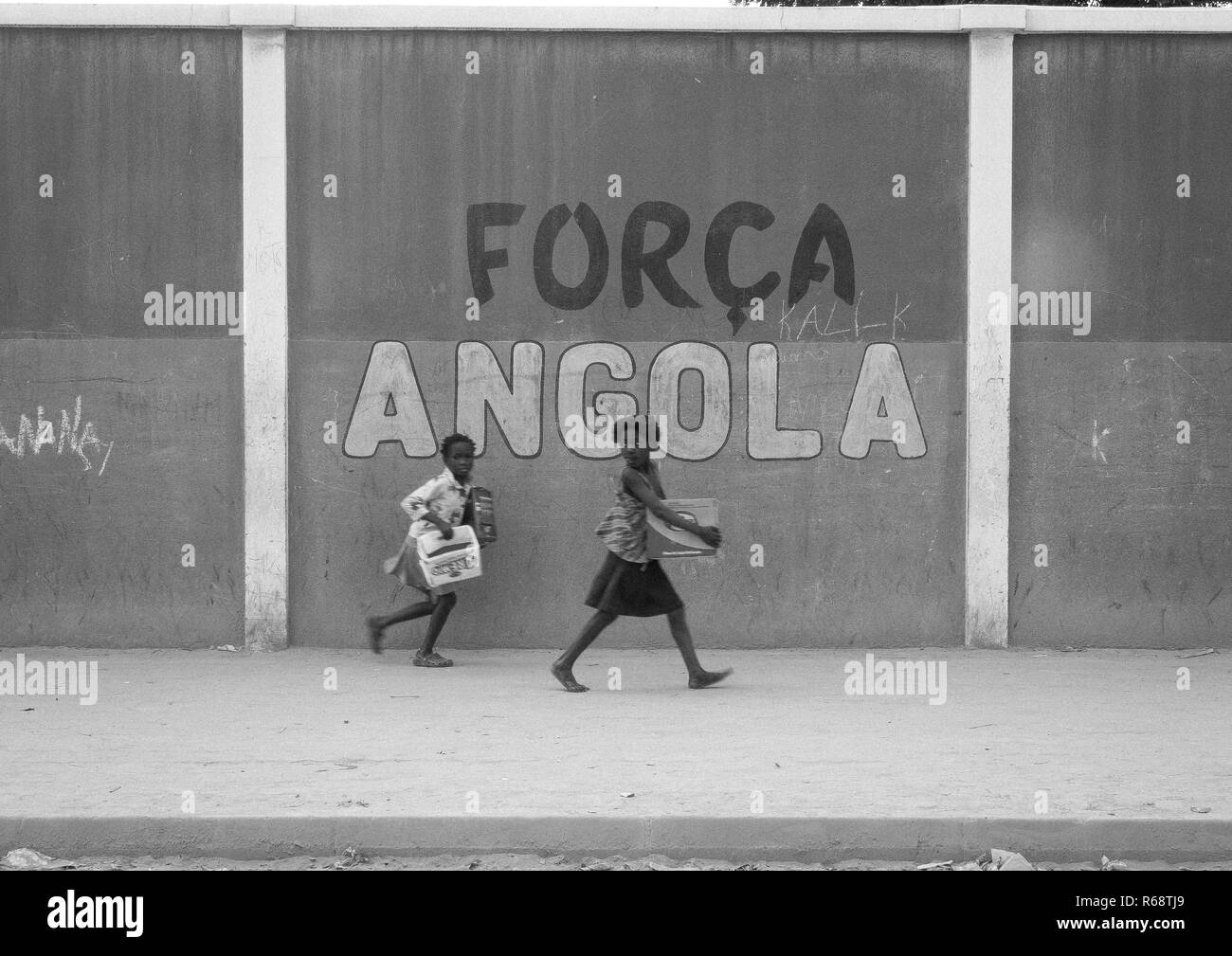 Girls walking in front of a wall with a nationalist slogan, Benguela Province, Catumbela, Angola - Stock Image
