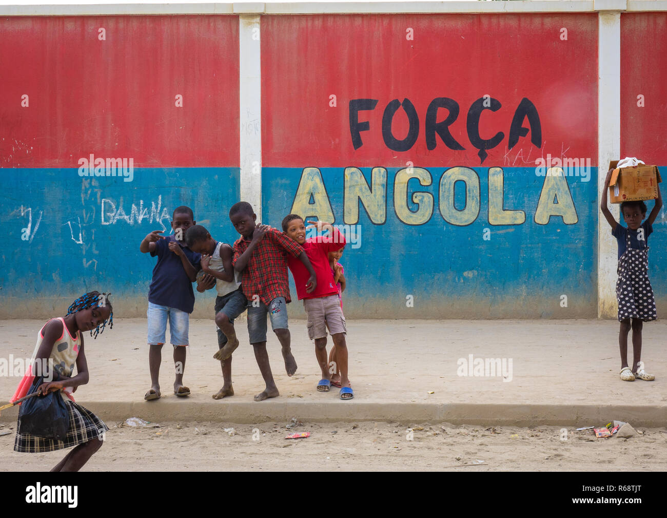 Kids walking in front of a wall with a nationalist slogan, Benguela Province, Catumbela, Angola - Stock Image