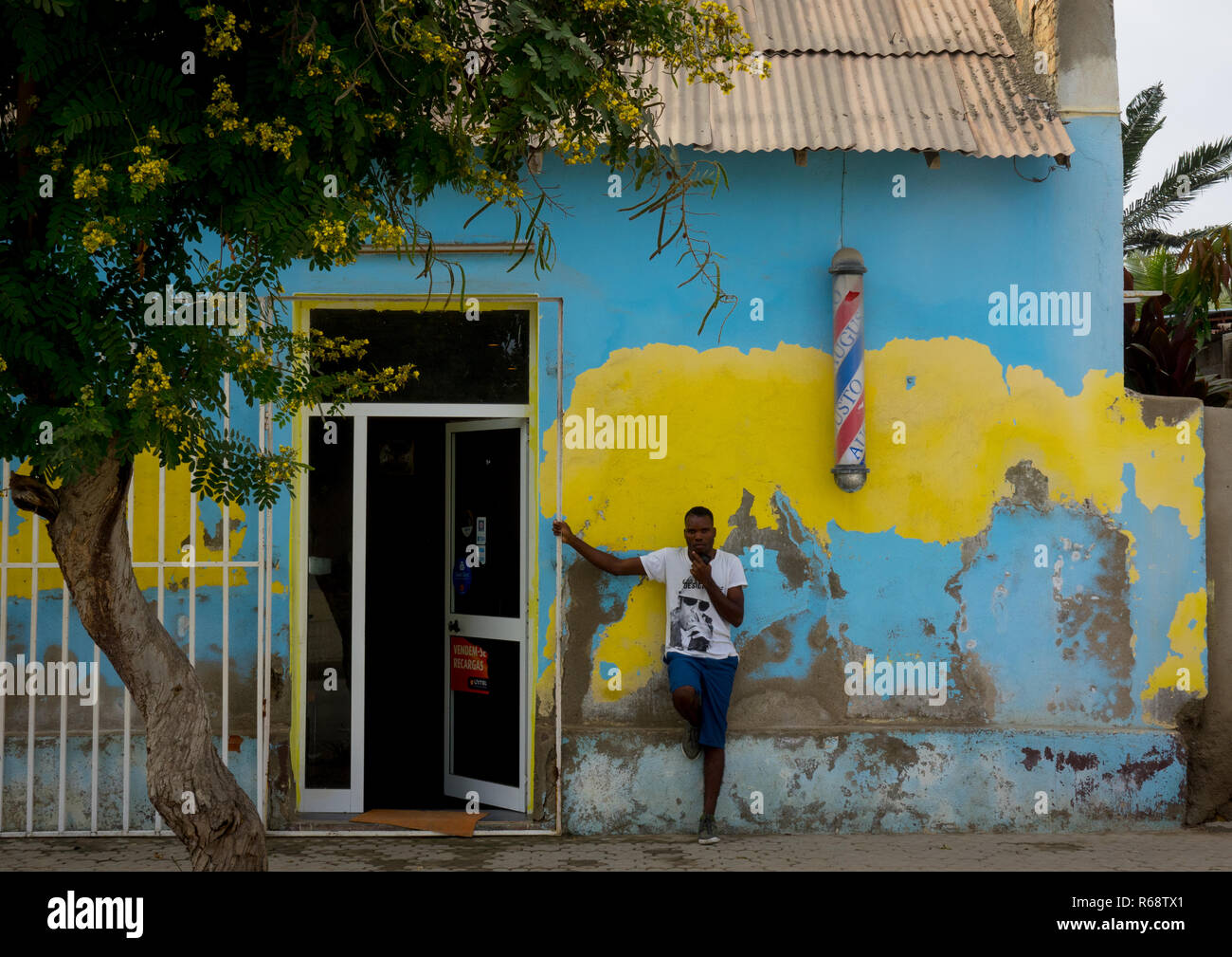 Man standing in front of a barber shop, Benguela Province, Benguela, Angola - Stock Image